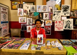 Photo: Patrick McKinnie Malcolm Johnson, one of the organizers of the inaugural Balboa-Con in the Outer Richmond District, sits in front of a comic art table set up in the lobby of the Balboa Theater. The 90-year-old theater hosted the event over several days.